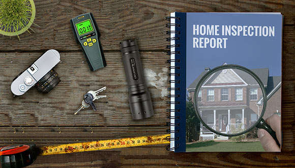 Various tools and a home inspection report on a wood surface